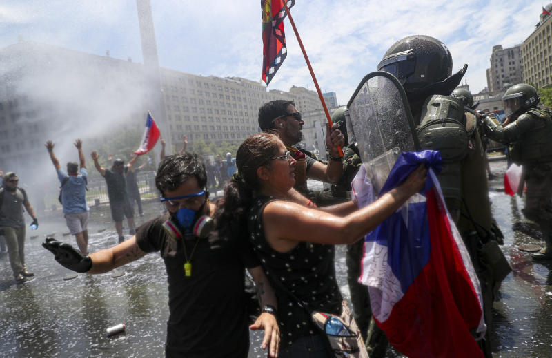 A woman places a Chilean flag on the riot shield of a Chilean police officer  during a protest march in front to La Moneda presidential palace in Santiago, Chile, Tuesday, Nov. 12, 2019. Students in Chile began protesting nearly a month ago over a subway fare hike. The demonstrations have morphed into a massive protest movement demanding improvements in basic services and benefits, including pensions, health, and education. (AP Photo/Esteban Felix)