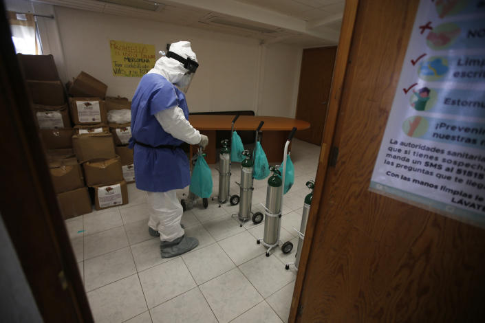 City worker Carlos Ruiz prepares tanks of oxygen for COVID-19 patients, in the Iztapalapa borough of Mexico City, Friday, Jan. 15, 2021. The city offers free oxygen refills for COVID-19 patients. (AP Photo/Marco Ugarte)