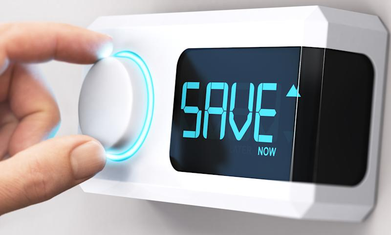 Hand turning a thermostat knob to increase savings by decreasing energy consumption. Source: Getty Images