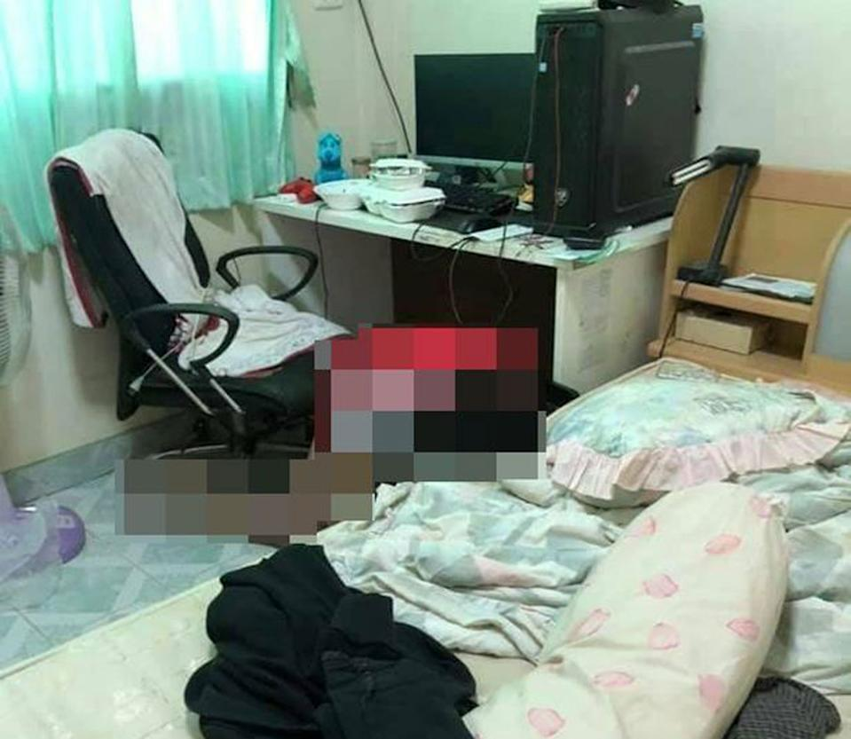 A bedroom is pictured. Takeaway food containers are seen on a desk which also has a computer. A bed is also seen. Piyawat Harikun's body, which is blurred, lies on the floor.