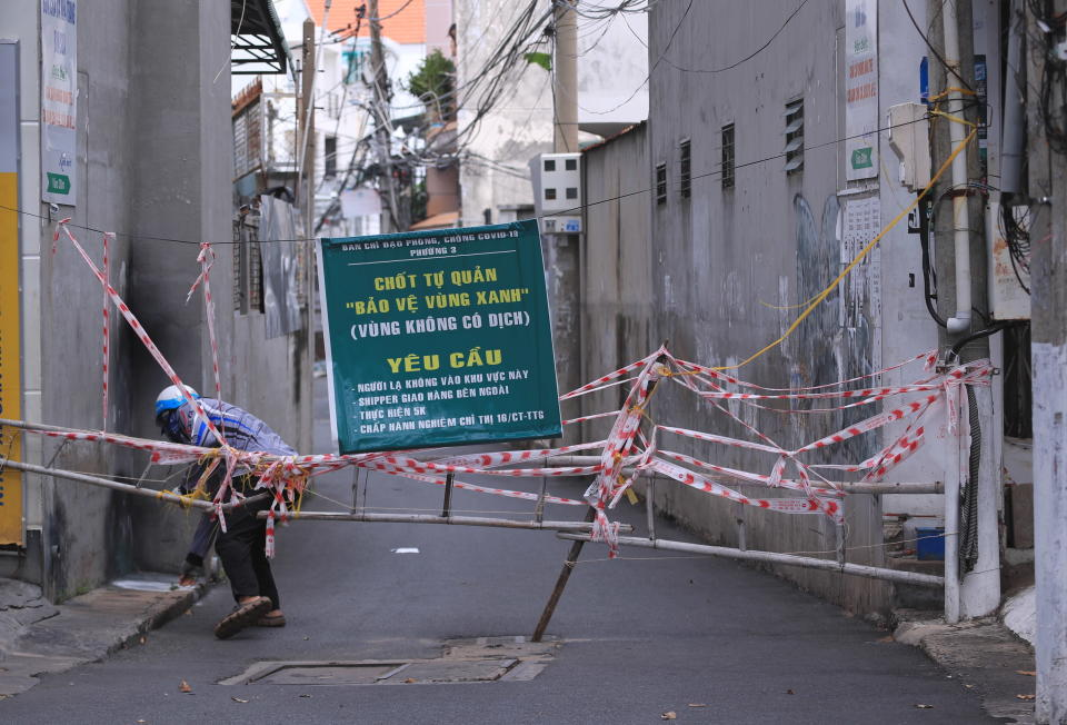 A man breaches through a barricade to get in an alley in Vung Tau, Vietnam, Monday, Sept. 20, 2021. The roadblocks and barricades make the streets of this southern Vietnamese city look like they did during the war that ended almost 50 years ago. But this time, the battle is being fought against the rampaging coronavirus.(AP Photo/Hau Dinh)