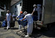 Workers unload food from a truck at a food distribution center in Rio de Janeiro, Brazil, on March 24, 2021