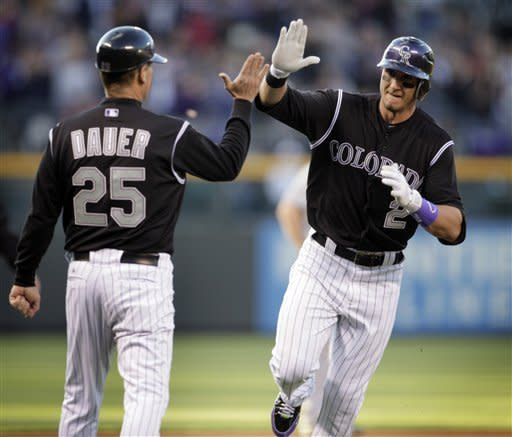CORRECTS COACH'S NAME TO RICH DAUER, NOT GABE BAUER - Colorado Rockies' Troy Tulowitzki (2) high-fives third base coach Rich Dauer after Tulowitzki hit a solo home run off New York Mets starting pitcher Chris Schwinden in the first inning of their baseball game in Denver on Friday, April 27, 2012. (AP Photo/Joe Mahoney)