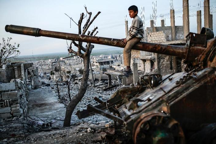 A Syrian Kurdish boy sits on a destroyed tank in the Syrian town of Kobane, also known as Ain al-Arab, on March 27, 2015 (AFP Photo/Yasin Akgul)