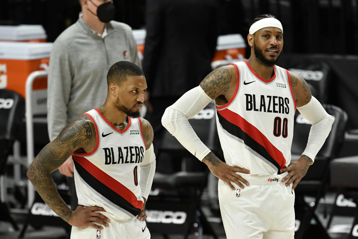 Damian Lillard and Carmelo Anthony stand on the court, both with their hands on their hips.