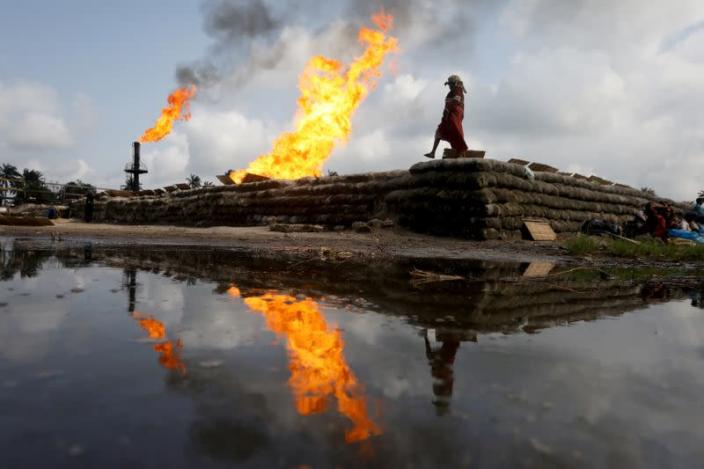 A reflection of two gas flaring furnaces and a woman walking on sand barriers is seen in the pool of oil-smeared water at a flow station in Ughelli, Delta State