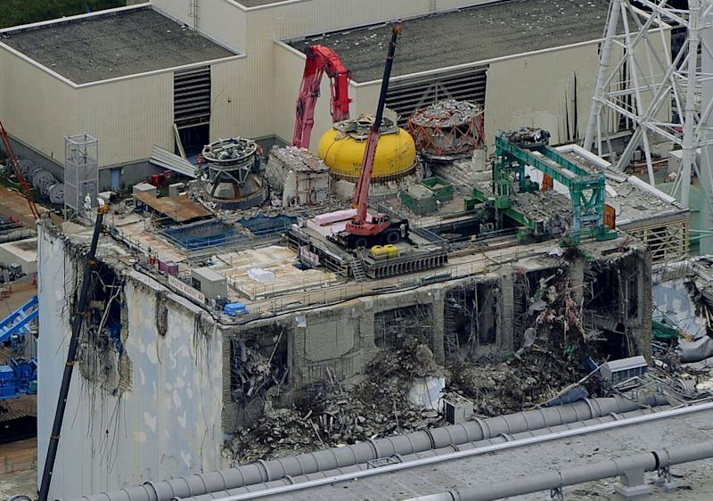 This aerial view shows the damaged No. 4 reactor building at Tokyo Electric Power Co.'s Fukushima Dai-ichi nuclear power plant in Okuma town, Fukushima prefecture, northeastern Japan, Wednesday, July 18, 2012. The operator of the tsunami-crippled nuclear plant in last year's disaster is taking two fuel rods out of a spent-fuel pool Wednesday to start dealing with a major remaining risk there. All of the 1,535 rods next to the reactor must eventually be removed from the pool to safer storage. (AP Photo/Kyodo News) JAPAN OUT, MANDATORY CREDIT, NO LICENSING IN CHINA, HONG KONG, JAPAN, SOUTH KOREA AND FRANCE