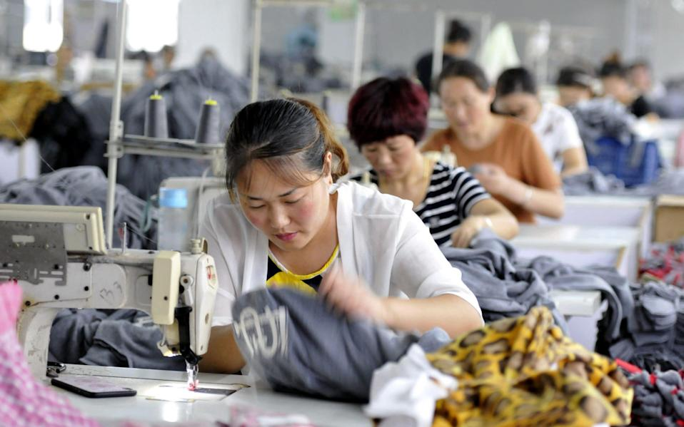 Employees working in a textile factory in Linyi in China's eastern Shandong province - STR/AFP/Getty Images