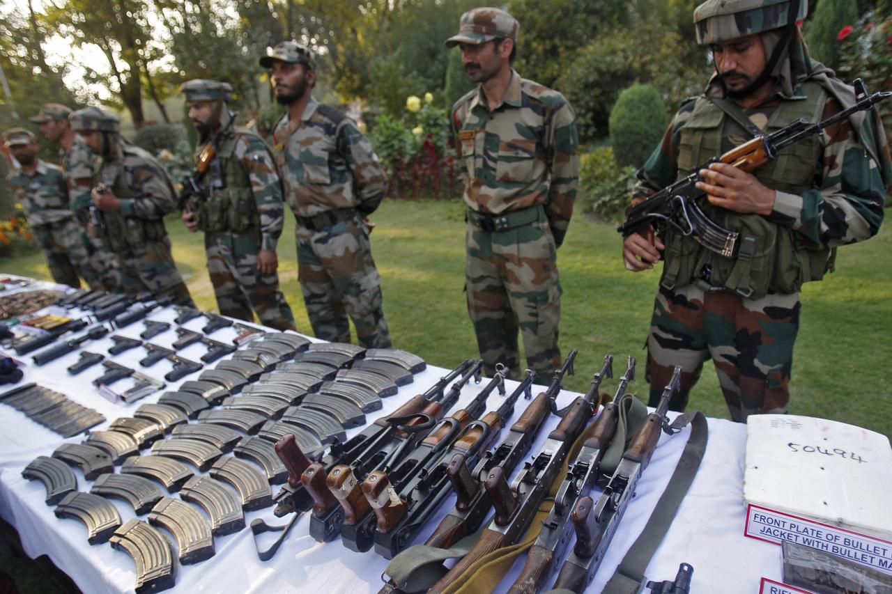 Indian army soldiers stand behind a display of seized arms and ammunition at a garrison in Srinagar, October 7, 2013. The Indian army on Monday displayed a cache of arms and ammunition, which according to them, were recovered from the Keran sector near the Line of Control (LoC) with Pakistan, on the 13th day of an operation. REUTERS/Danish Ismail (INDIAN-ADMINISTERD KASHMIR - Tags: MILITARY)