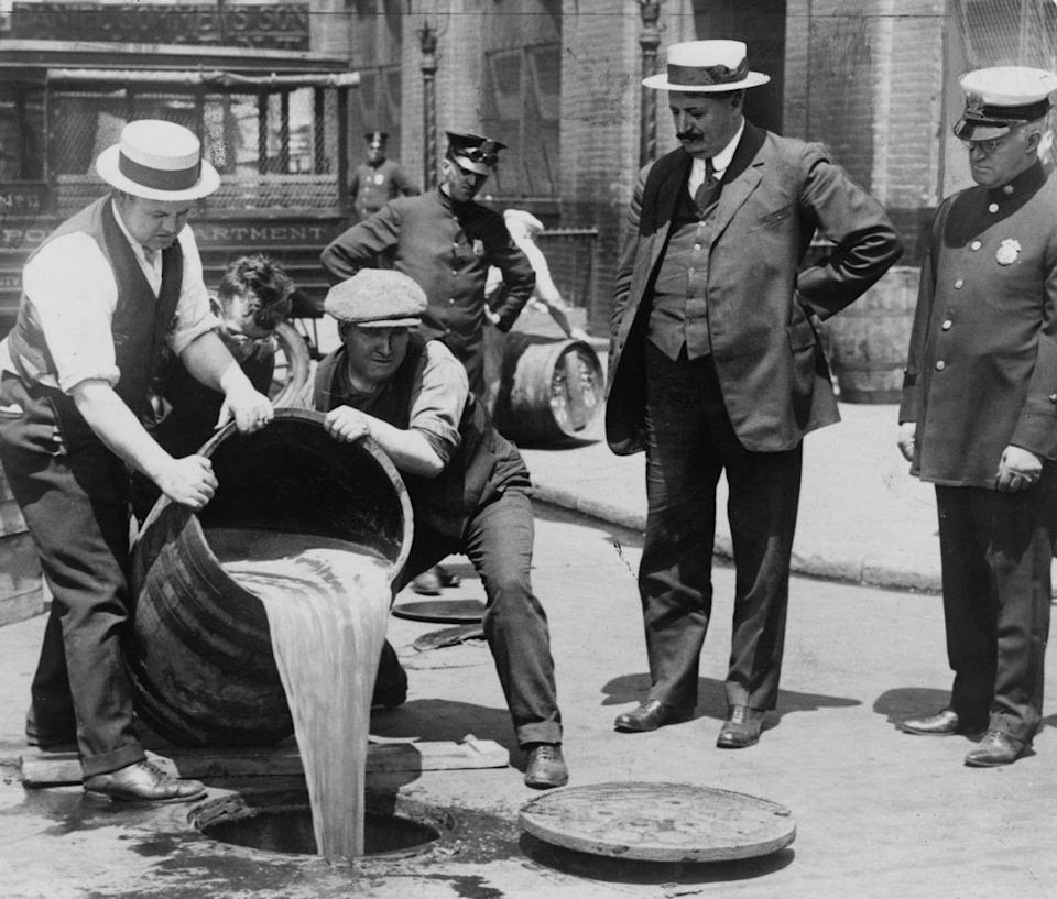 "<p>New York City police officers supervise a pair of men as they dump a barrel of illegal alcohol into a sewer. Prohibition in the United States lasted from 1920 to 1933.</p><p>Related: <a href=""https://www.esquire.com/lifestyle/g20969723/old-new-york-city-vintage-photos/"" rel=""nofollow noopener"" target=""_blank"" data-ylk=""slk:What New York City Looked Like the Year You Were Born"" class=""link rapid-noclick-resp"">What New York City Looked Like the Year You Were Born</a></p>"