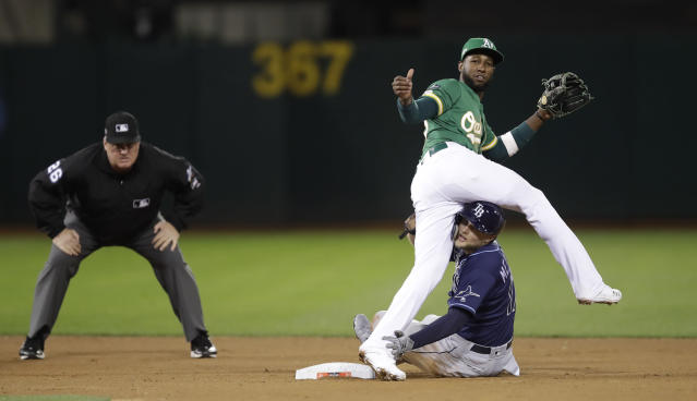 Oakland Athletics' Jurickson Profar straddles Tampa Bay Rays' Austin Meadows after a failed double play in the eighth inning of an American League wild-card baseball game Wednesday, Oct. 2, 2019, in Oakland, Calif. Rays' Travis d'Arnaud was safe at first base. (AP Photo/Ben Margot)
