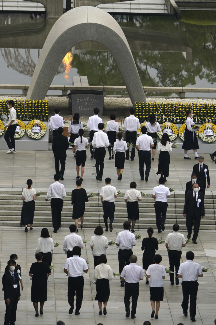 The family of the deceased offer flowers to Hiroshima Memorial Cenotaph during the ceremony to mark the 75th anniversary of the bombing at the Hiroshima Peace Memorial Park Thursday, Aug. 6, 2020, in Hiroshima, western Japan. (AP Photo/Eugene Hoshiko)