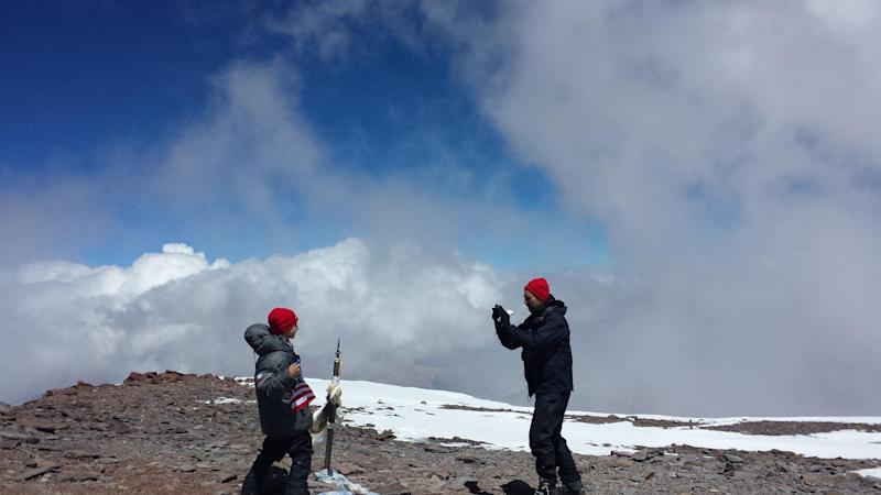 This Dec. 24, 2013 photo released by Lhawang Dhondup shows Kevin Armstrong, right, taking a picture of his 9-year-old son Tyler on the the summit of Aconcagua mountain in Argentina. Tyler, from Southern California, became the youngest person in recorded history to reach the summit when he reached it on Christmas Eve with his father Kevin and a Tibetan sherpa, Lhawang Dhondup, who has climbed Mt. Everest multiple times. (AP Photo/Lhawang Dhondup)