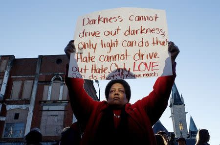 Barbara Carter of Tuscaloosa holds a sign as she waits to join a commemorative march across the Edmund Pettus Bridge in Selma, Alabama, in this file photo taken January 18, 2015. REUTERS/Tami Chappell