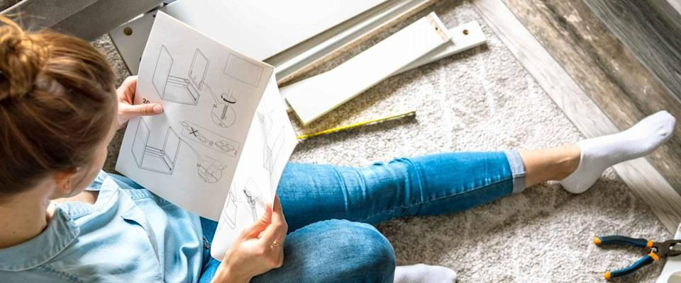 Concentrated young woman reading the instructions to assemble furniture at home in the living room
