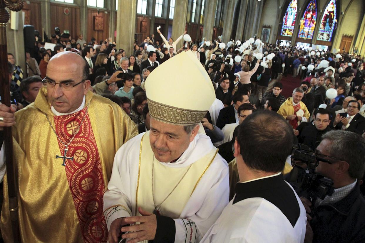 Bishop Juan Barros, center, attends his first religious service as citizens protest at the Osorno cathedral south of Santiago on March 21, 2015. (Photo: Carlos Gutierrez / Reuters)
