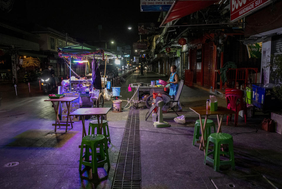 FILE - In this Jan. 4, 2021, file photo, a lone street vender waits for customers at Khao San road, a once popular hangout with bars and entertainment for locals and tourists in Bangkok, Thailand. Now, an outbreak at nightspots in the capital Bangkok has sent new infections surging, suggesting the country may have been lulled into a false sense of security before mass vaccinations begin. (AP Photo/Gemunu Amarasinghe, File)