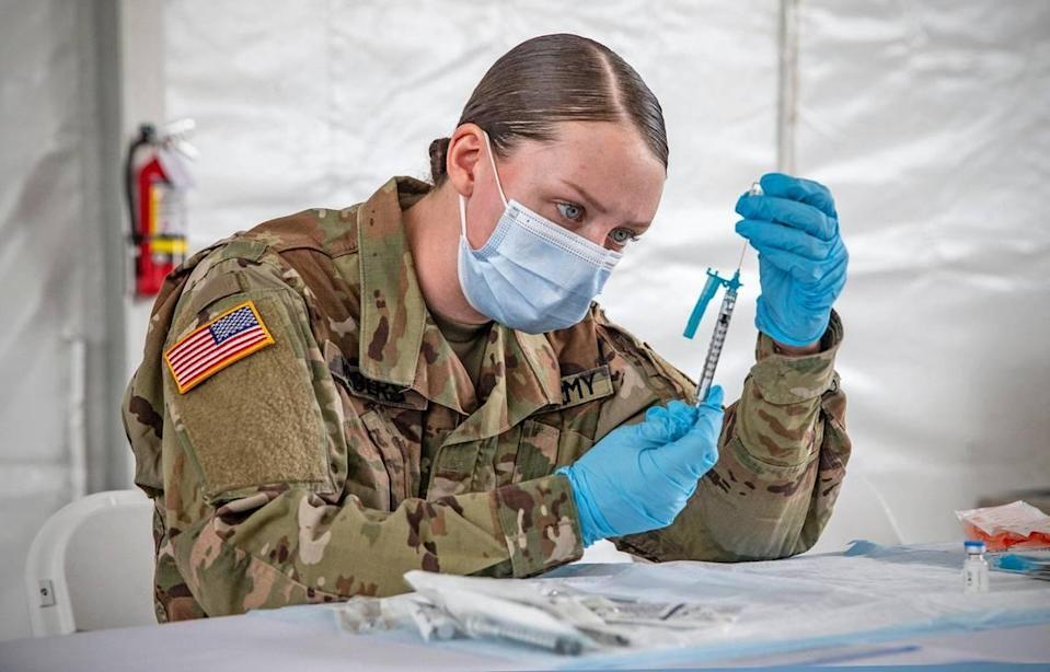 U.S. Army Medic, Kristen Rogers, prepares a COVID-19 needle for injection during opening day at the FEMA vaccination site on Miami-Dade College's North Campus on Wednesday, March 3, 2021.