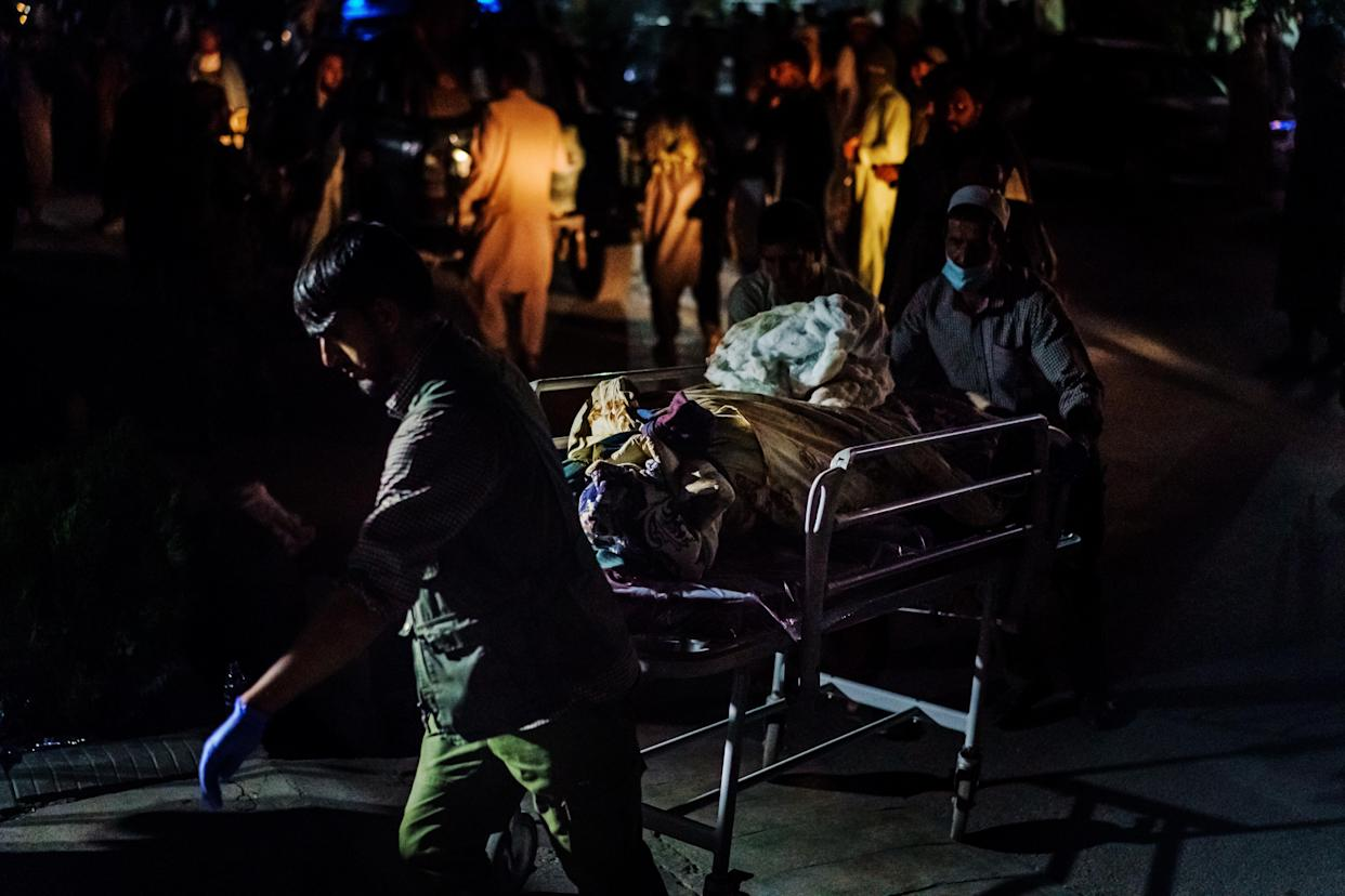 Hospital  staff rolls in a casualty that was brought by Taliban fighters at Emergency Hospital in Kabul, Afghanistan, Thursday, Aug. 26, 2021. (Marcus Yam/Los Angles Times via Getty Images)