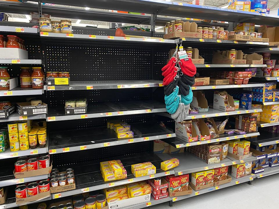 empty shelves with some products in a walmart