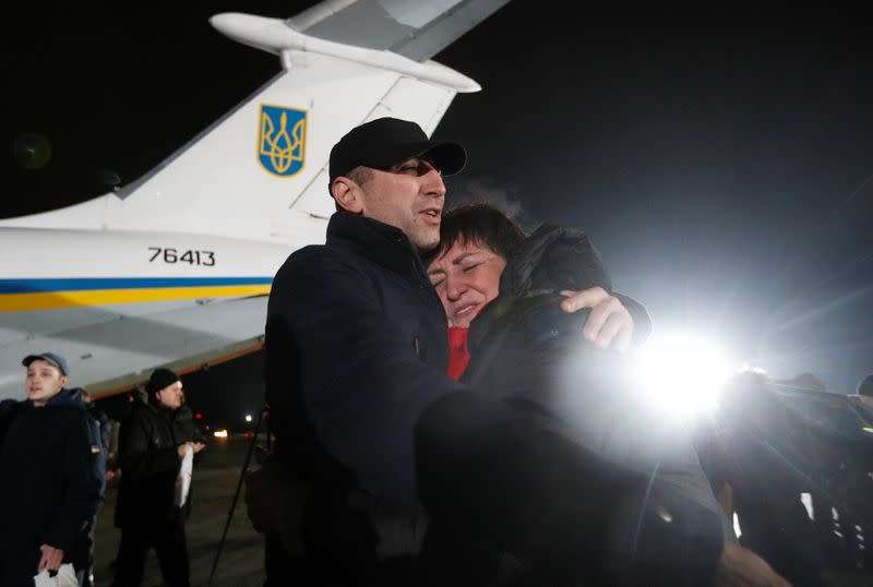 A Ukrainian citizen exchanged during a prisoners of war swap embraces a relative at an airport outside Kiev