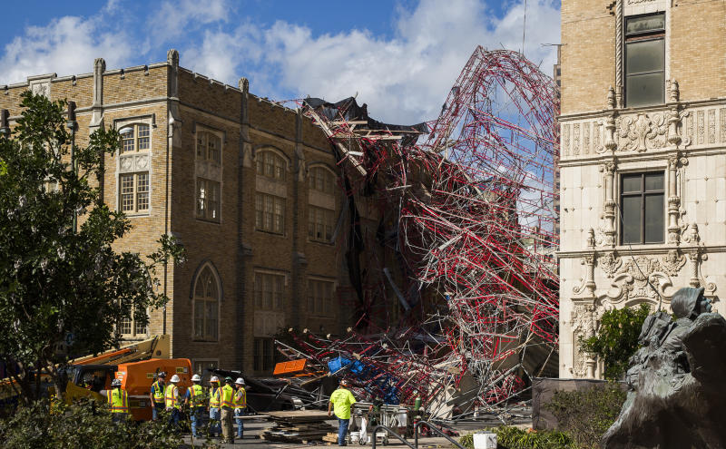 Construction workers begin cleaning up collapsed scaffolding on the 300 block of East Martin Street Friday, Sept. 20, 2019 in San Antonio. Officials say three bystanders were slightly hurt as a 100-foot (30-meter) section of scaffolding collapsed on a San Antonio street amid 50 mph (80 kph) winds from a system linked to Tropical Storm Imelda. The scaffolding, along a high-rise building, crushed several parked vehicles and crashed into St. Mark's Episcopal Church. (Daniel Carde/The San Antonio Express-News via AP)