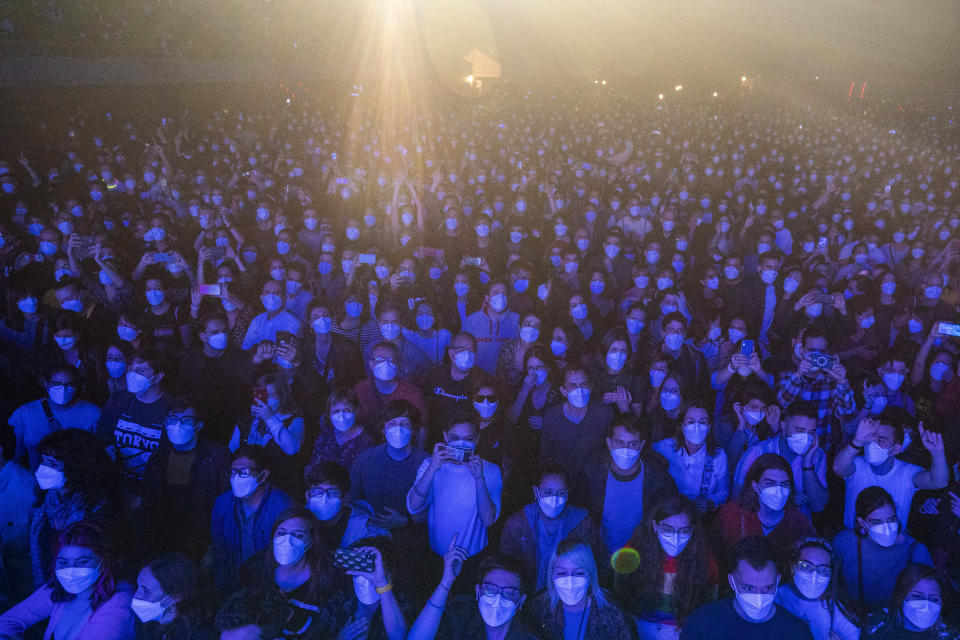 People using face masks take part in a music concert in Barcelona, Spain, Saturday, March 27, 2021. Five thousand music lovers are set to attend a rock concert in Barcelona on Saturday after passing a same-day COVID-19 screening to test its effectiveness in preventing outbreaks of the virus at large cultural events. The show by Spanish rock group Love of Lesbian has the special permission of Spanish health authorities. While the rest of the country is limited to gatherings of no more than four people in closed spaces, the concertgoers will be able to mix freely while wearing face masks. (AP Photo/Emilio Morenatti)
