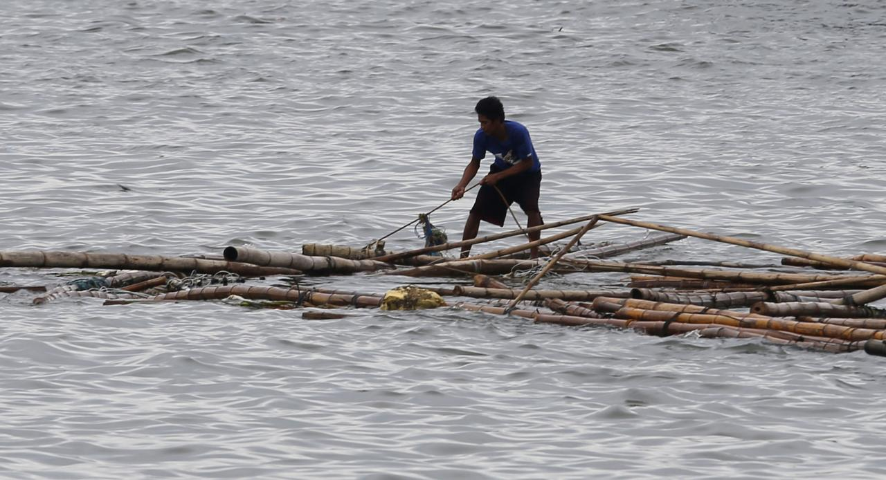 A fisherman recovers bamboo poles from a fish pen destroyed at the height of Typhoon Kalmaegi near Roxas Boulevard in Manila Bay September 15, 2014. A strong typhoon slammed into the rice-producing Philippine northern region on Sunday, cutting power and communications lines and forcing people to flee to higher ground, national disaster agency officials said. REUTERS/Erik De Castro (PHILIPPINES - Tags: SOCIETY DISASTER ENVIRONMENT)