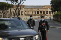 Carabinieri police officers stop a car at a road block near the Colosseum, in downtown Rome, Saturday, April 3, 2021. Italy went into lockdown on Easter weekend in its effort to battle then Covid-19 pandemic. (AP Photo/Gregorio Borgia)