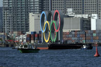 The Olympic Symbol is transported on a barge in the Odaiba section Tuesday, Dec. 1, 2020, in Tokyo. The five Olympic rings are back in Tokyo Bay. They were removed for maintenance four months ago shortly after the Tokyo Olympics were postponed until next year because of the COVID-19 pandemic. (AP Photo/Eugene Hoshiko)