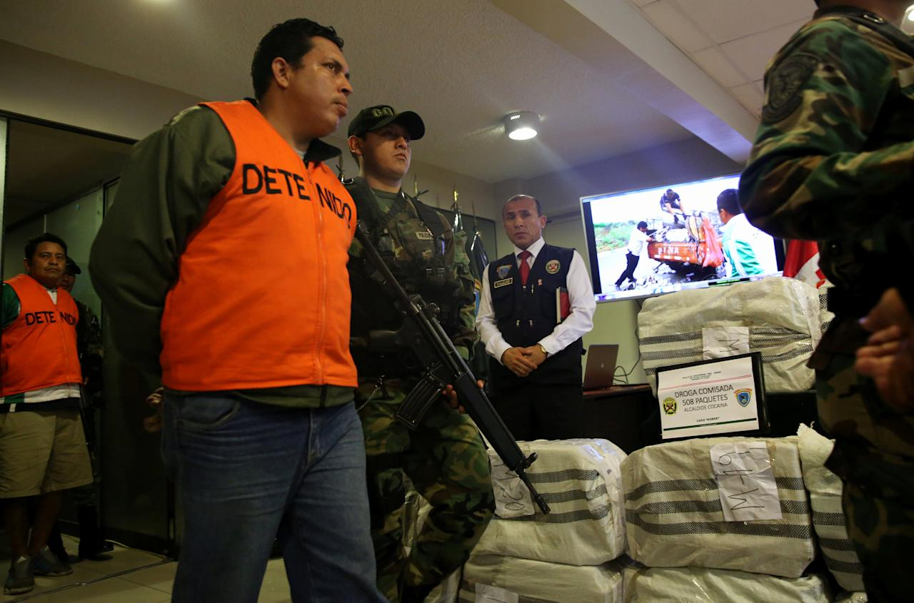 Peruvian police escort detainees after seizing cocaine during an operation, at the Peruvian police headquarters in Lima, Peru July 11, 2017. REUTERS/Mariana Bazo