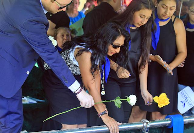 <p>Esmeralda Leal, mother of Frank Hernandez, lays a white rose on the casket of her son as friends and family attend the burial at Highland Memorial Park in Weslaco, Texas, June 18, 2016. (Joel Martinez/The Monitor via AP) </p>