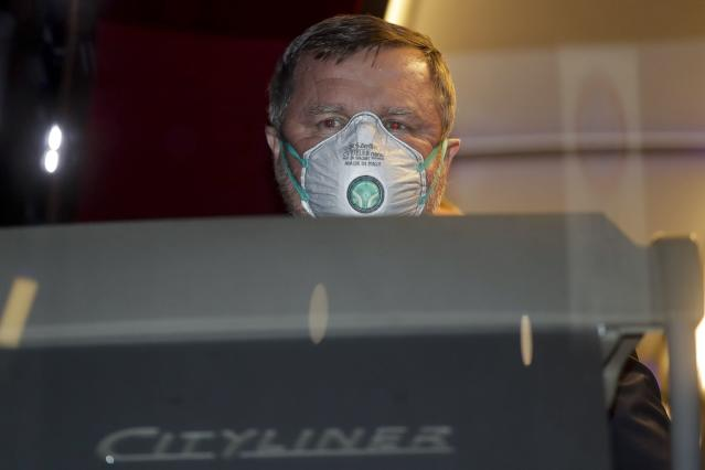 Bulgarian soccer team Ludogorets coach Pavel Vrba wears a protective face masks as he sits in the coach bus heading to the San Siro stadium, in Milan, Italy, Thursday, Feb. 27, 2020. Ludogorets is playing Italian club Inter Milan in a Europa League soccer match on Thursday that is scheduled to go ahead in an empty stadium due to the coronavirus outbreak. (AP Photo/Luca Bruno)