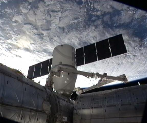 The privately built SpaceX Dragon cargo capsule is moved into its final position on the International Space Station's Harmony module with a bright Earth in the background in this view captured during the capsule's March 3, 2013, docking. The Dr
