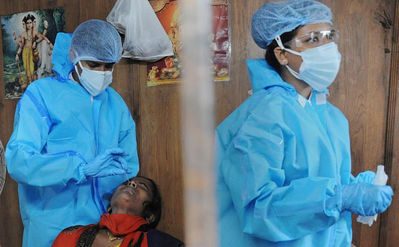 Nurses in India conduct Covid tests.