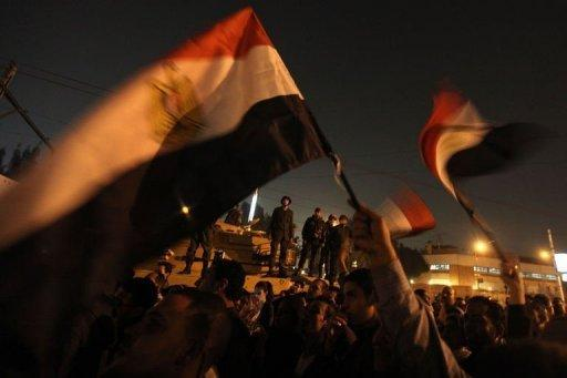 <p>Egyptian soldiers stand on top of a tank as opposition supporters and protesters wave national flags outside the presidential palace in Cairo. Rival mass protests have been called for next Tuesday in Egypt over a bitterly disputed constitutional referendum, raising the potential for more violent street clashes in a sharpening political crisis.</p>