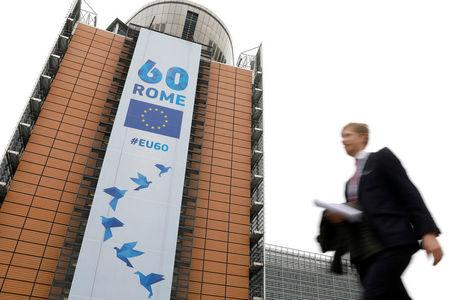 A man walks past the European Commission headquarters in Brussels on which is displayed a banner celebrating the 60 years after the signing of the Treaty of Rome, in Brussels