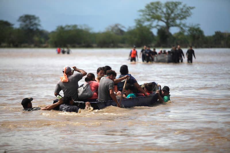 FILE PHOTO: Flood-affected people get on a boat to cross a street after passage of Storm Eta, in La Lima