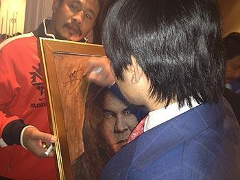 Manny Pacquiao signs a portrait of Muhammad Ali on Saturday at a brain damage research benefit