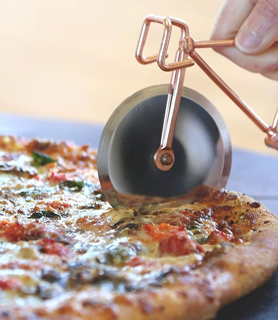 """Heather here: Youshould probably invest in this if you religiously order a pie or two every weekend (ahem, me).I have this pizza cutter, and while I could've easily gotten a standard one to do the same job, this one brings me joy *and* works well. Can't ask for much more than that!<br /><br /><strong>Promising review:</strong>""""So cute and beautiful at the same time!!<strong>Sharp and cut the pizza like butter.</strong>Bought as a gift and will definitely buy again!!"""" —<a href=""""https://www.amazon.com/dp/B074WBJZGL?tag=huffpost-bfsyndication-20&ascsubtag=5817703%2C40%2C43%2Cd%2C0%2C0%2C0%2C962%3A1%3B901%3A2%3B900%3A2%3B974%3A3%3B975%3A2%3B982%3A2%2C16178346%2C0"""" target=""""_blank"""" rel=""""noopener noreferrer"""">Amazon Customer</a><br /><br /><strong>Get it from Amazon for <a href=""""https://www.amazon.com/dp/B074WBJZGL?tag=huffpost-bfsyndication-20&ascsubtag=5817703%2C40%2C43%2Cd%2C0%2C0%2C0%2C962%3A1%3B901%3A2%3B900%3A2%3B974%3A3%3B975%3A2%3B982%3A2%2C16178346%2C0"""" target=""""_blank"""" rel=""""noopener noreferrer"""">$22.88</a>.</strong>"""