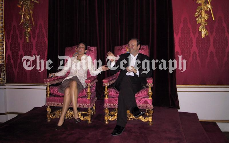 Ghislaine Maxwell and Kevin Spacey sitting on thrones belonging to the Queen and the Duke of Edinburgh at Buckingham Palace in 2002 - THE TELEGRAPH