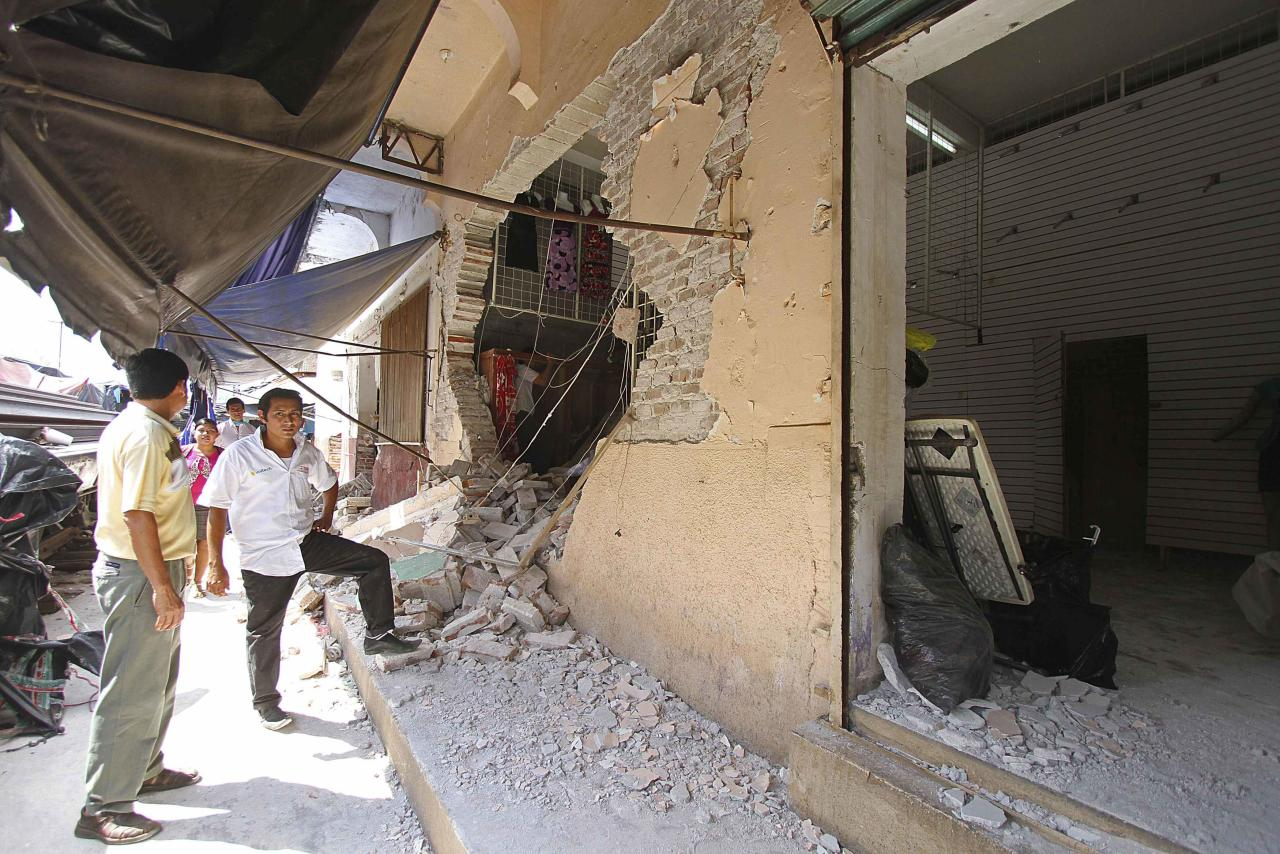 Residents stand outside a clothing store damaged by an earthquake at the town of Huixtla, in the Mexican state of Chiapas July 7, 2014. A strong earthquake shook the border between Guatemala and Mexico on Monday, killing at least three people, including a newborn boy, damaging dozens of buildings and triggering landslides. Much of the damage from the 6.9-magnitude quake was reported in the Guatemalan border region of San Marcos, where it downed power lines, cracked buildings and triggered landslides that blocked roads. REUTERS/Mario Castillo (MEXICO - Tags: ENVIRONMENT DISASTER)