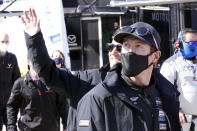 Scott Dixon, right, of New Zealand and Reneger van der Zande, left, acknowledge fans in the Fan Zone as they walk back to their garage after a practice session for the Rolex 24 hour race at Daytona International Speedway, Friday, Jan. 29, 2021, in Daytona Beach, Fla. (AP Photo/John Raoux)