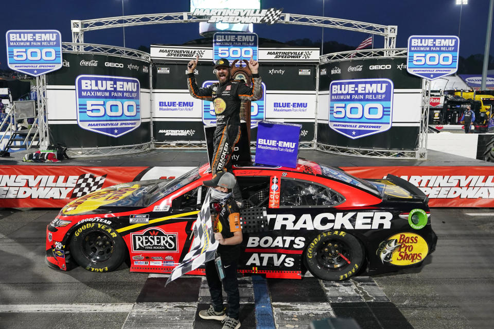Martin Truex Jr., top, celebrates after winning a NASCAR Cup Series auto race at Martinsville Speedway in Martinsville, Va., Sunday, April 11, 2021. (AP Photo/Steve Helber)