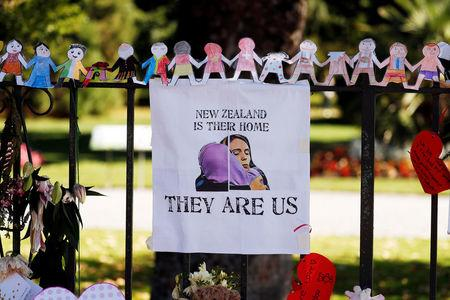 A poster hangs at a memorial site for victims of Friday's shooting, in front of Christchurch Botanic Gardens in Christchurch