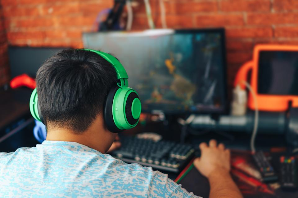The gamer sits on a gaming chair and plays computer games. The player has green headphones on his head.