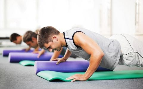 Group of young people doing Pilates exercises - Credit: skynesher/Vetta