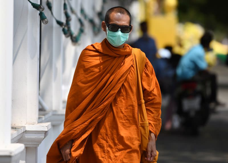 A Buddhist monk wears a protective mask as he walks in Bangkok