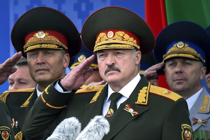 FILE In this file photo taken on Tuesday, July 3, 2018, Belarus President Alexander Lukashenko, center, attends a military parade marking Independence Day in Minsk, Belarus. Belarus' authoritarian President Alexander Lukashenko faces a perfect storm as he seeks a sixth term in the election held Sunday, Aug. 9, 2020 after 26 years in office. Mounting public discontent over the worsening economy and his government's bungled handling of the coronavirus pandemic has fueled the largest opposition rallies since the Soviet collapse. (Sergei Gapon/Pool Photo via AP, File)