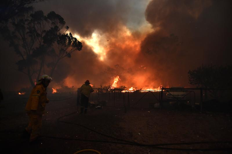 Rural Fire Service (RFS) crews engage in property protection of a number of homes along the Old Hume Highway as the Green Wattle Creek Fire threatens a number of communities in the south west of Sydney, Thursday.